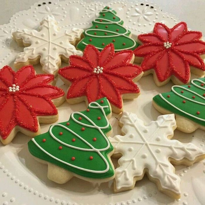 cookies in the shape of christmas trees, snowflakes and flowers, decorated with white green and red icing, royal icing recipe for sugar cookies