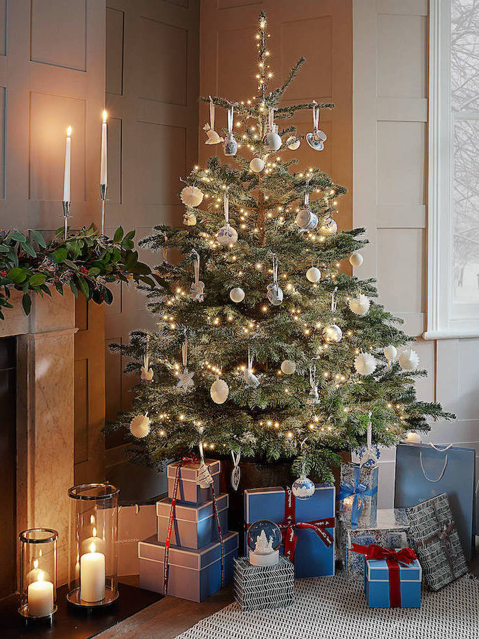wrapped presents underneath a tree, silver and gold ornaments, christmas decorations indoor ideas, tree with lots of lights