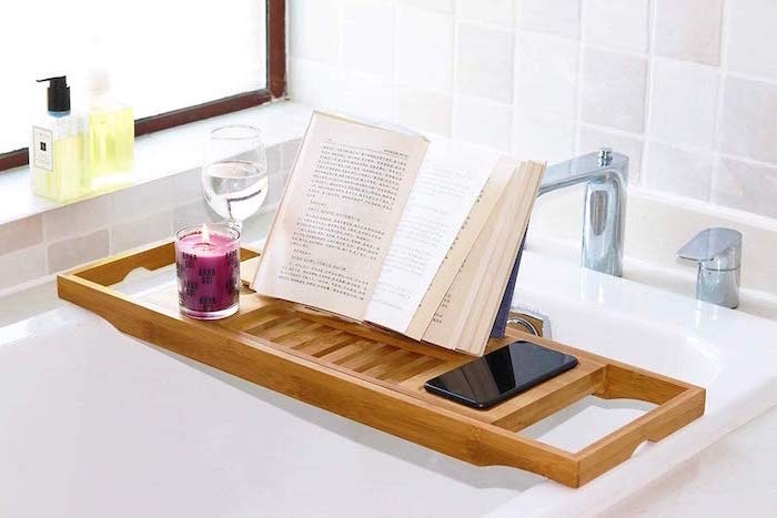 wooden bathtub caddy tray, placed over white bath tub, book and candle on top, meaningful gifts for mom, white tiles