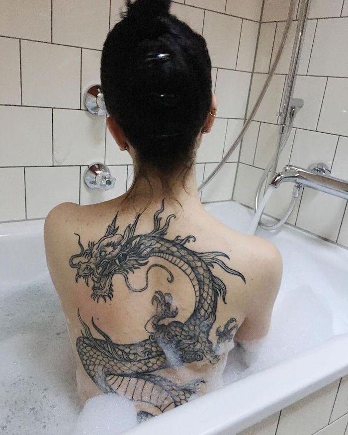 dragon thigh tattoo, large back tattoo, on woman sitting in bathtub, with black hair in a messy bun