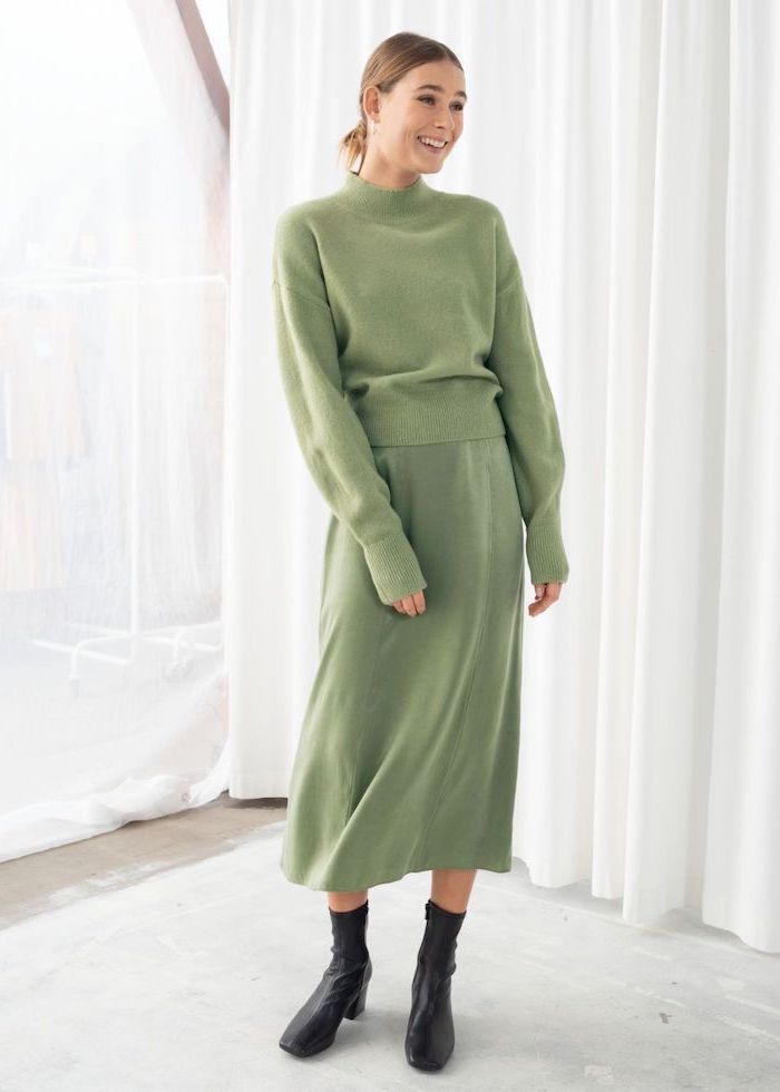 fall styles for women, woman smiling, wearing green skirt and sweater, black boots, white background