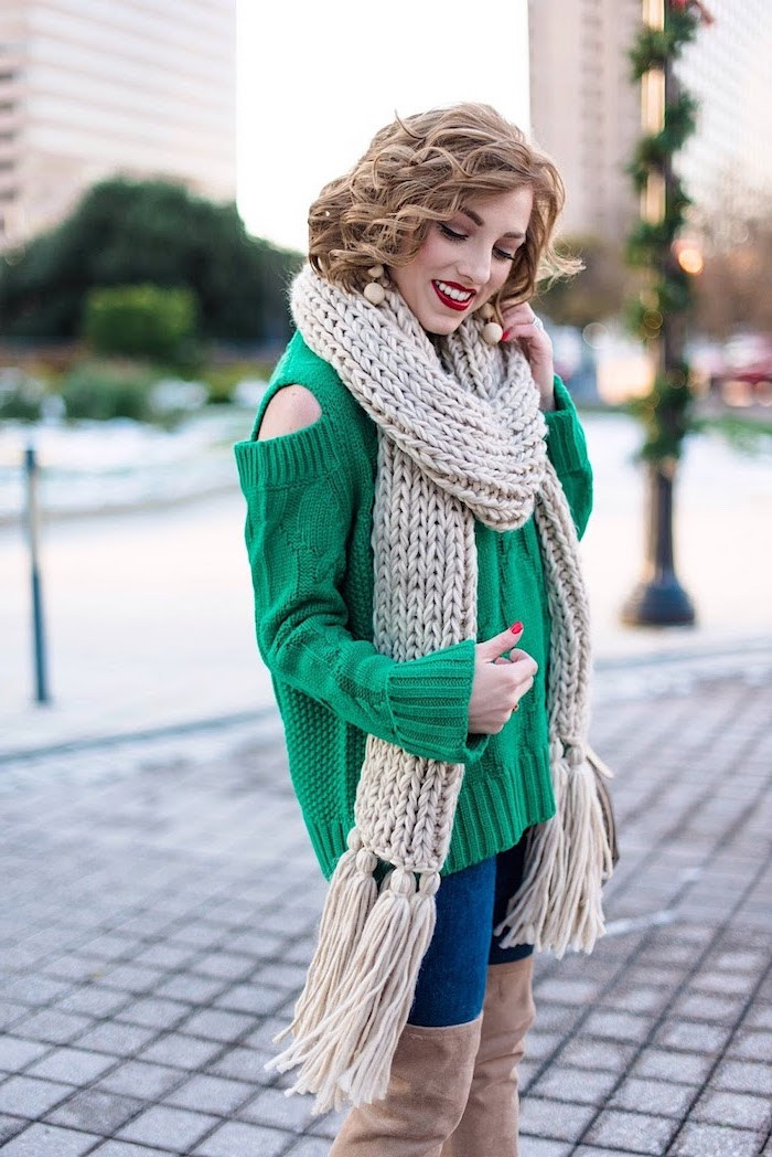 woman wearing green sweater, jeans and knee high boots, best christmas gifts for mom, large beige knitted scarf