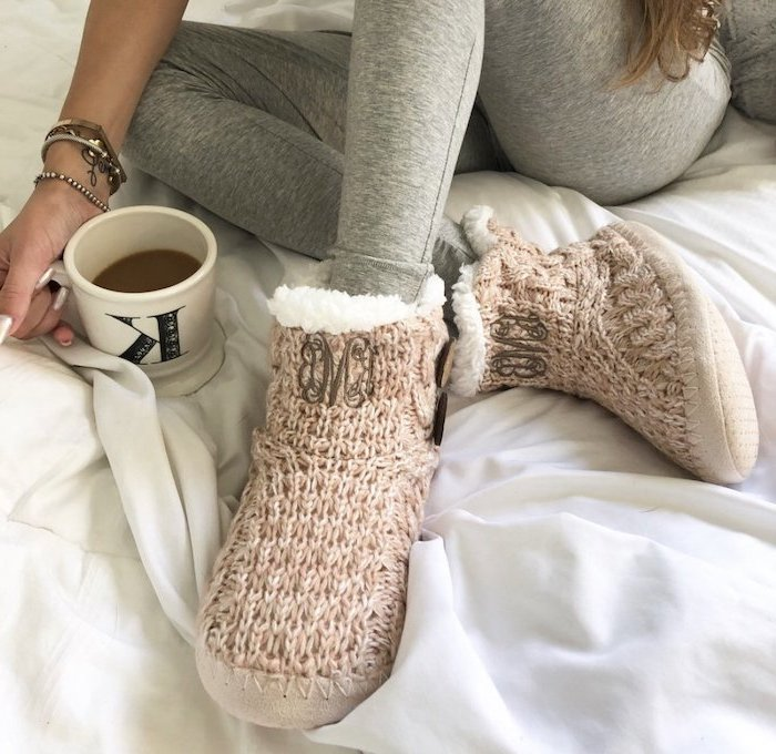 what to get mom for christmas, woman sitting in bed, wearing grey tights and knitted slippers, holding a coffee mug