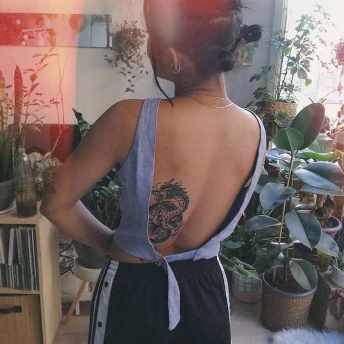 woman wearing black pants, open back denim top, dragon thigh tattoo, back tattoo, black hair, lots of plants in the background