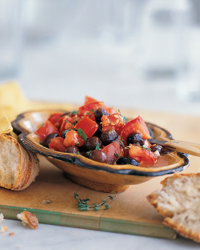 ceramic bowl filled with salad, chopped tomatoes and black beans, placed on wooden board, christmas party snacks