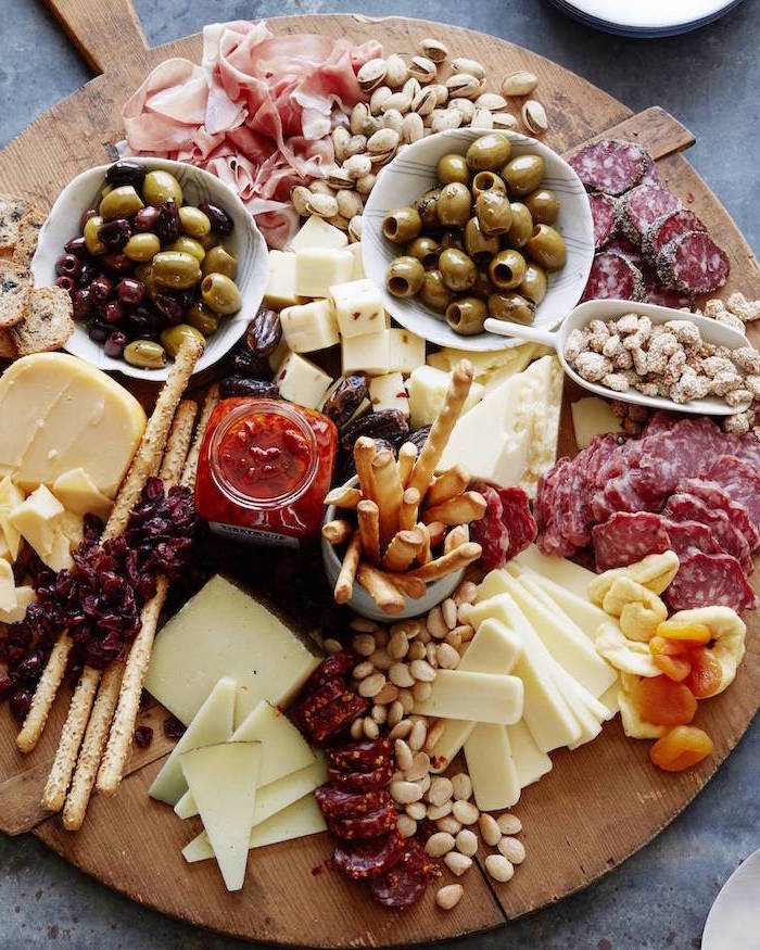 large round wooden board, cheese and meat on it, bowls of olives, christmas party snacks, crackers and pretzels