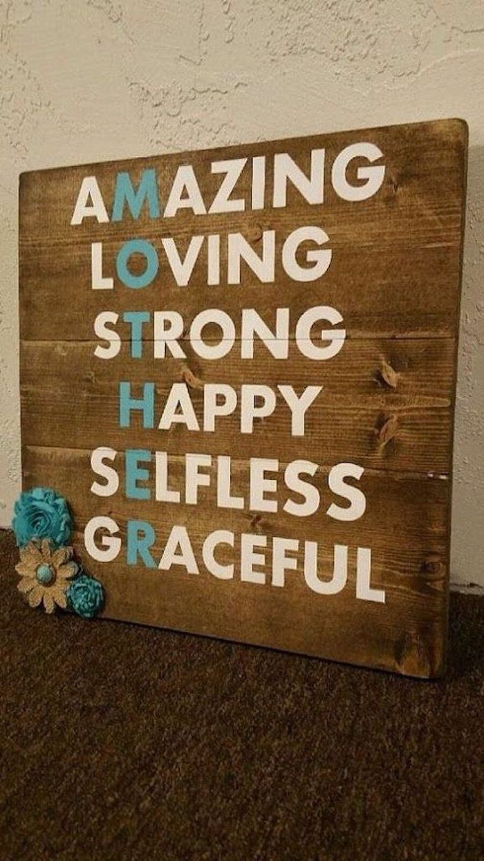 wooden board with adjectives written on it, forming the word mother, meaningful gifts for mom, leaning on white wall