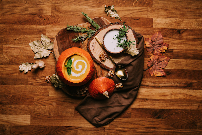 wooden table, fall arrangement on it, cream of chicken soup recipe, pumpkin soup poured inside a carved pumpkin