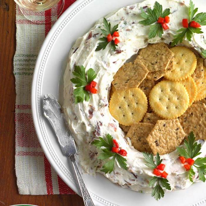 wreath made of bacon and cheese dip, crackers in the middle, christmas party snacks, placed on white plate