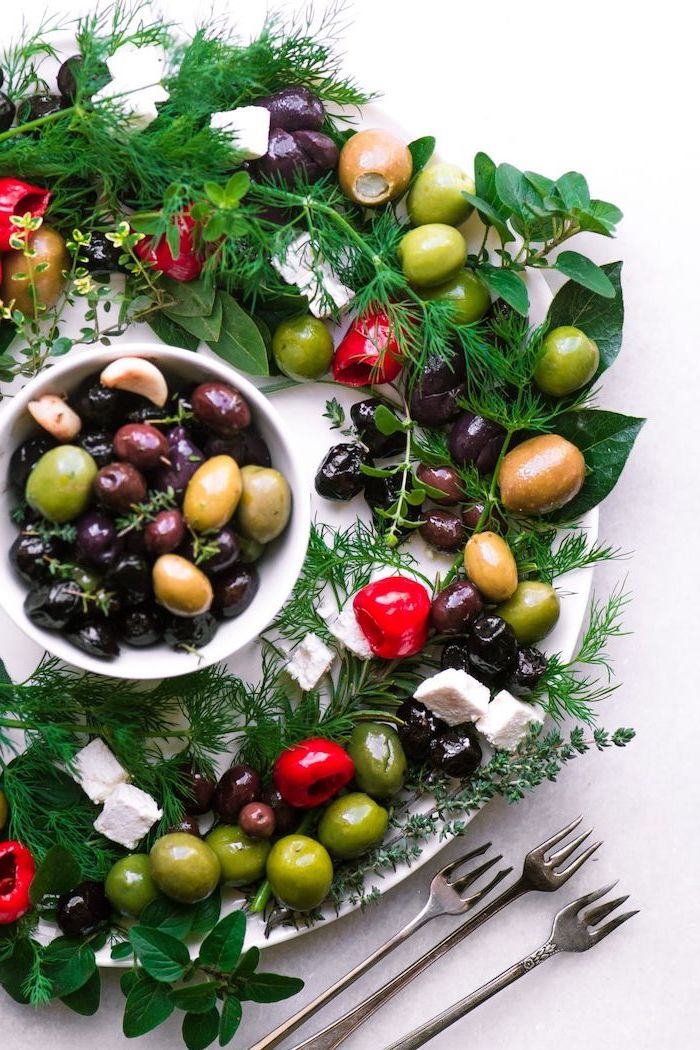 christmas party food ideas finger foods, wreath made of herbs, olives and feta cheese, bowl of olives in the middle