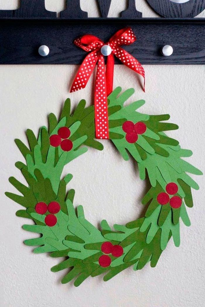 christmas wreath made of handprints, cut out of green paper, hung with red ribbon, homemade christmas crafts