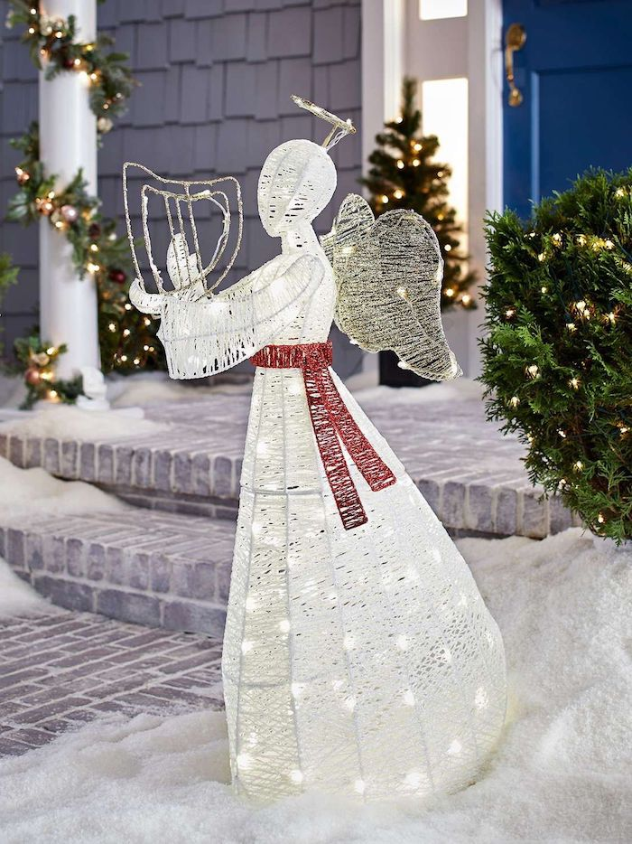 angel figurine, intertwined with lights, large outdoor christmas decorations, red ribbon tied around it, placed in the snow