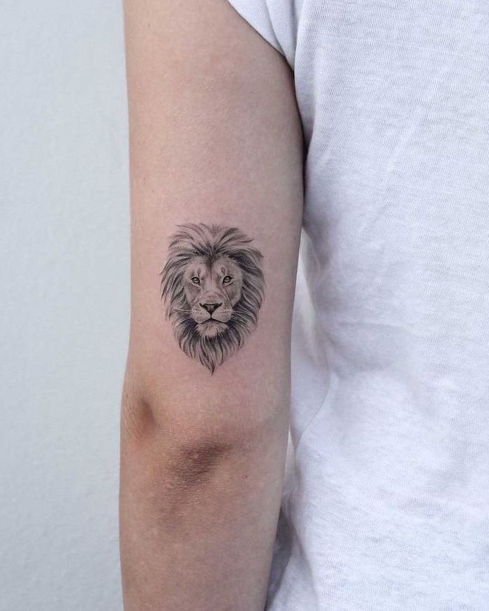 lion tattoo, back of arm tattoo, small lion head with mane, tattoo on woman wearing white t shirt