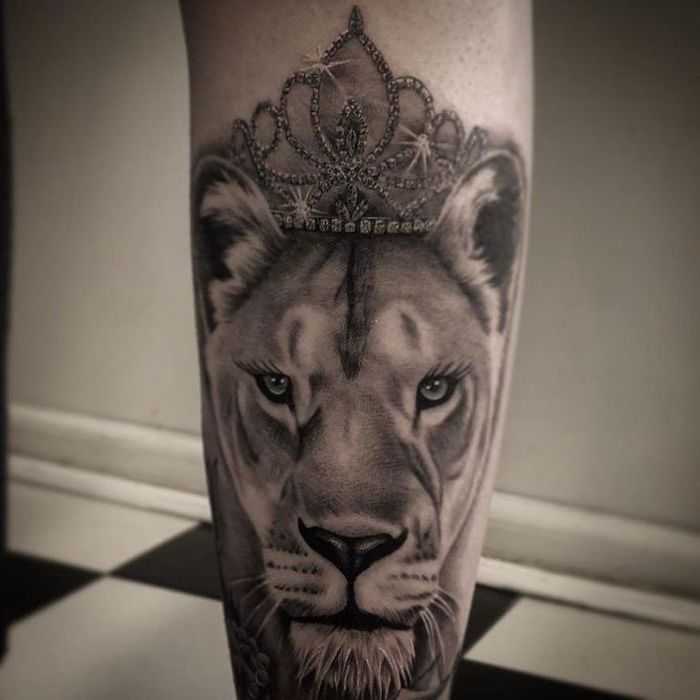 back of leg tattoo, lioness head with sparkling crown on top, lioness tattoo, black and white photo