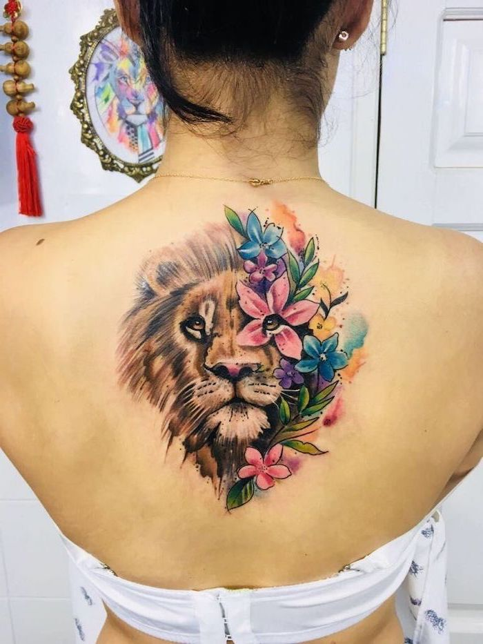 lion head with mane, half of it covered with flowers, lioness tattoo, watercolor back tattoo, on woman with black hair