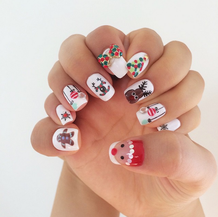 short squoval nails with white nail polish, different christmas theme decorations on each nail, winter nail colors