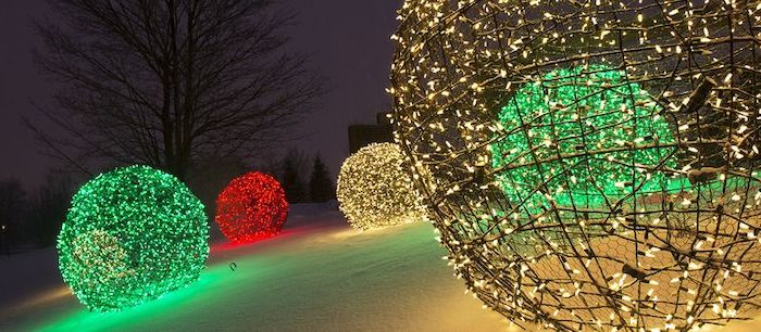large baubles made of chicken wire, outdoor christmas decorations, lights in different colors intertwined with the wire