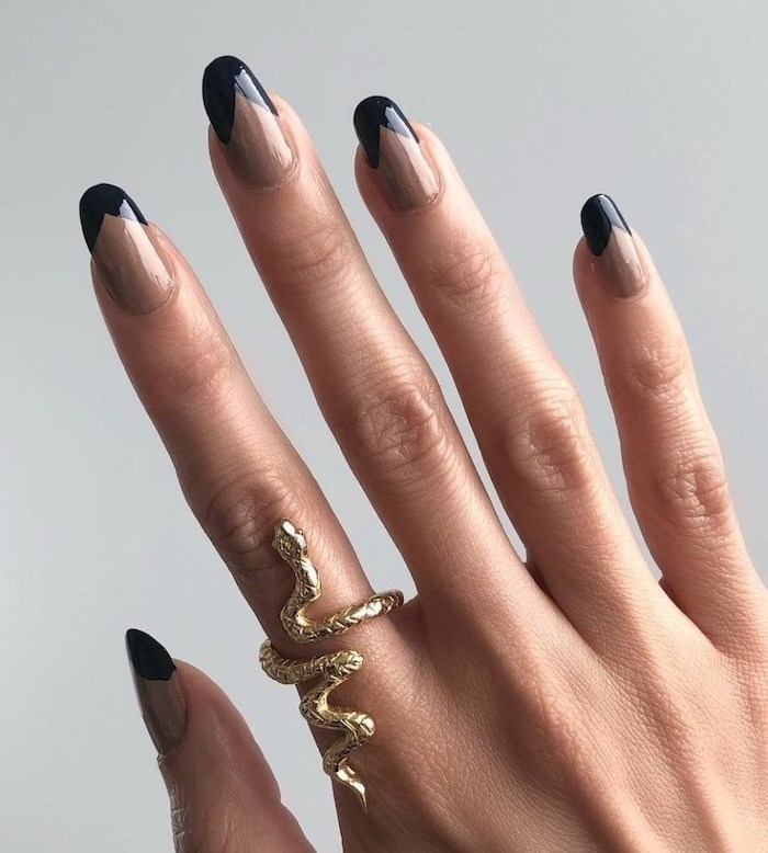 long nails with beige nail polish, black french manicure, winter nail colors, female hand with gold snake ring on the index finger