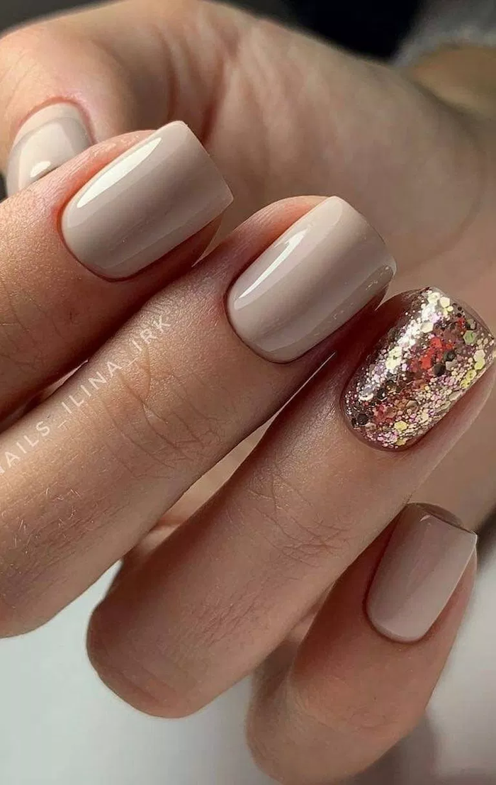 nude nail designs, gold glitter nail polish on the ring finger, short square nails