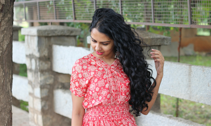 woman with long curly black hair, hair color trends 2020, woman wearing red floral dress