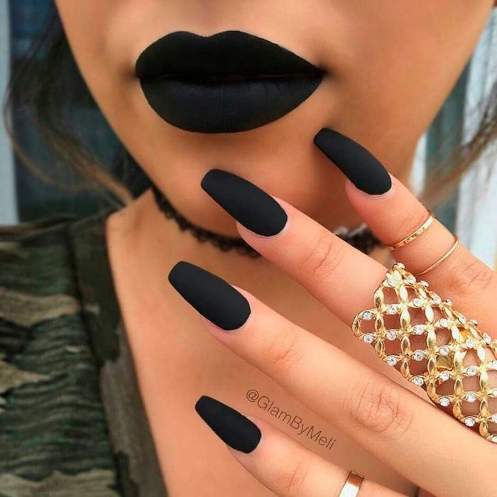 woman with black matte lipstick, long nails with black matte nail polish, white and gold nails, large golden ring