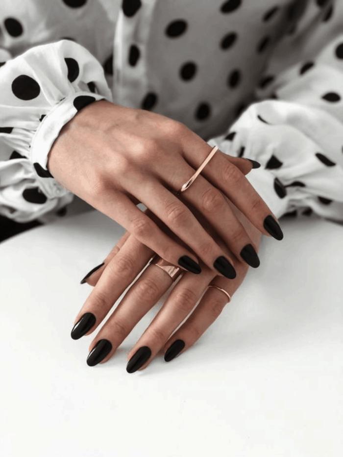 woman with almond nails, wearing white shirt with black polka dots, winter nail colors, black nail polish
