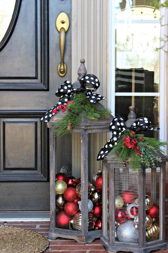 two wooden lanterns, filled with baubles, black ribbons with white polka dots on top, large outdoor christmas decorations