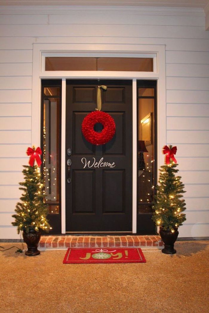 red wreath hanging on the door, outdoor christmas tree lights, two small trees with lights and red ribbons, on both sides of the door