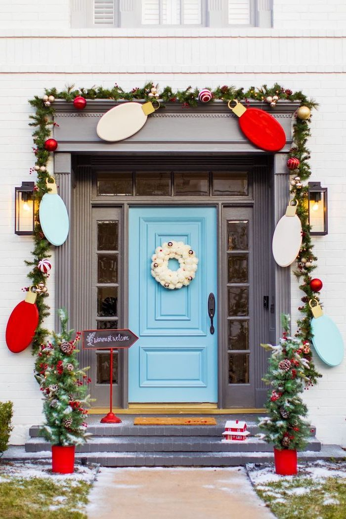wreath with red baubles, hanging over the door frame, outdoor christmas tree lights, blue door with white wreath