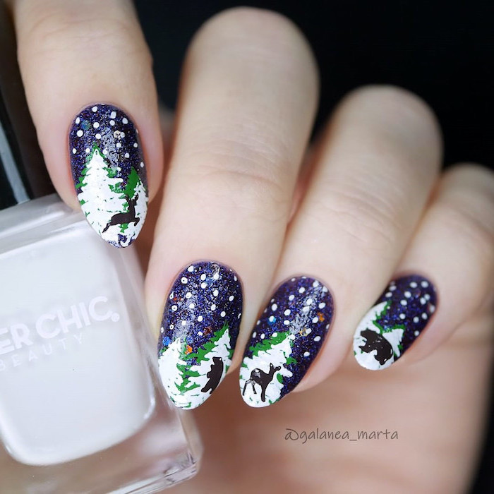 blue glitter nail polish on almond nails, white and gold nails, snowy trees decorations on each nail