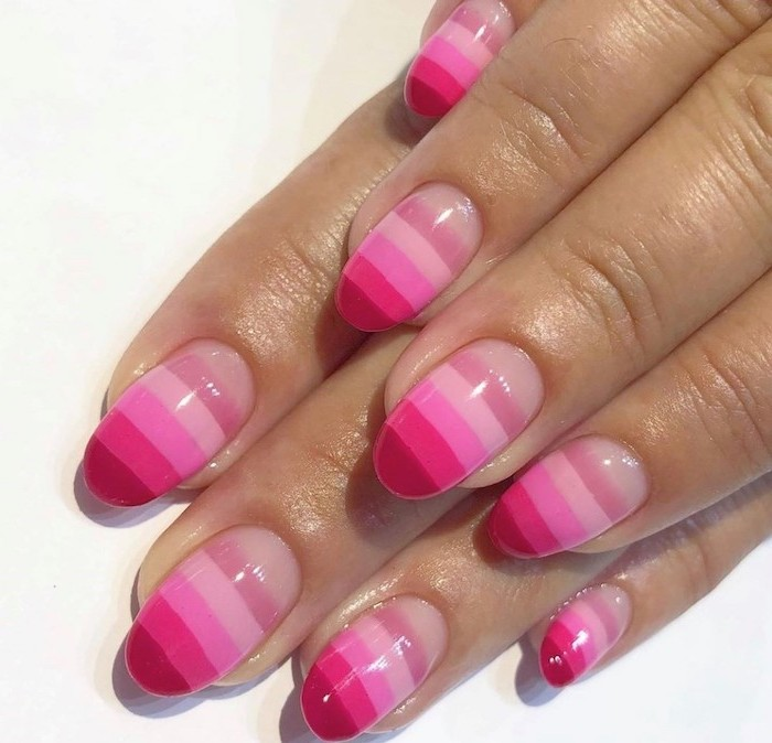 all shades of pink nail polish on each nail, short almond nails, glitter ombre nails, white background