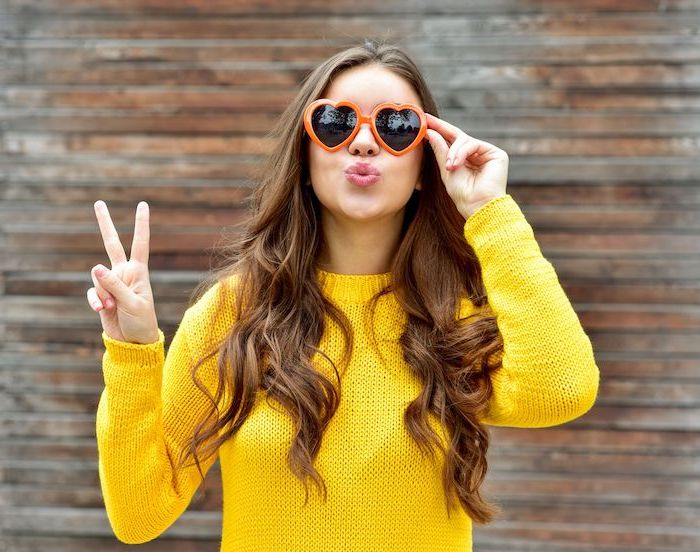 woman wearing yellow knitted sweater, heart shaped orange sunglasses, hair color trends 2020, long brown wavy hair