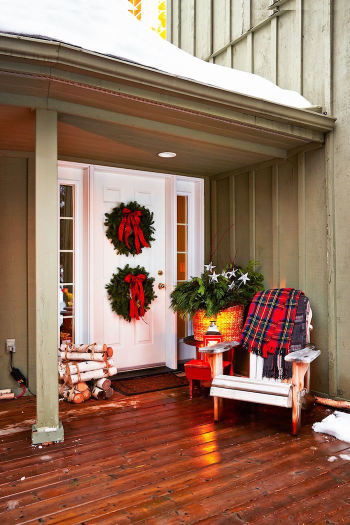 wooden chair with plaid blanket on the porch, outdoor christmas decorations, two christmas wreaths with red ribbons on the door