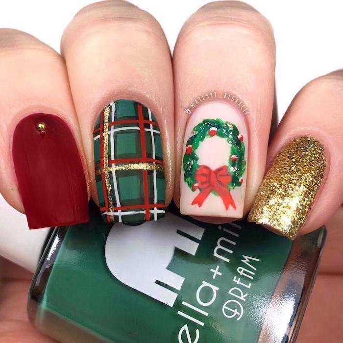 christmas theme decorations on each nail, different color nails, red green and gold glitter nail polish, wreath decoration on ring finger