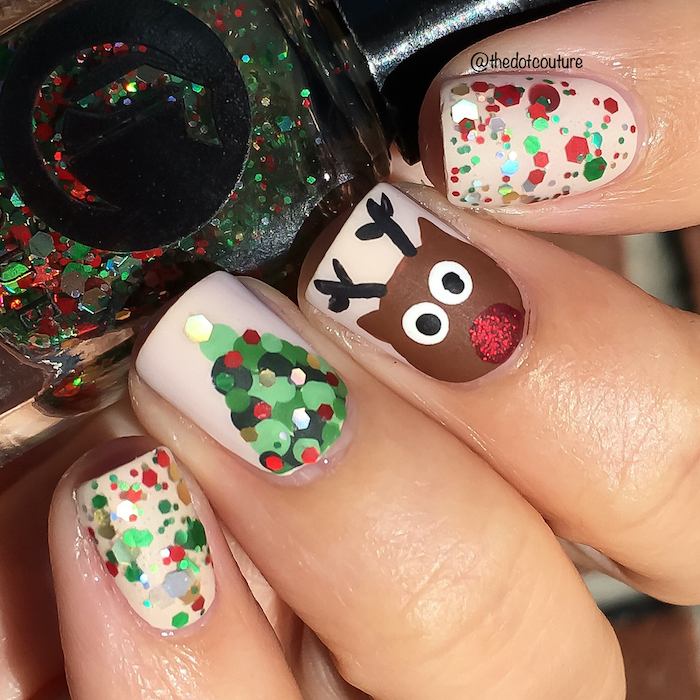 christmas themed decorations on short nails, beige nail polish, nail colors, hand holding a nail polish bottle