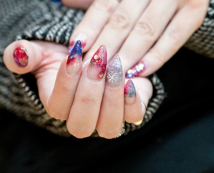 stiletto nails, blue red silver glitter nail polish, different decorations with rhinestones on each nail, different color nails