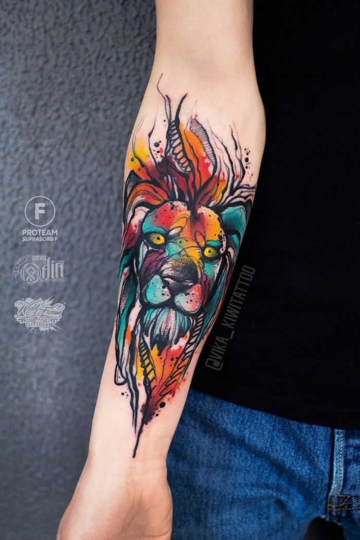 lion forearm tattoo, lion head with mane, watercolor forearm tattoo, mane in different colors, on woman wearing jeans and black top