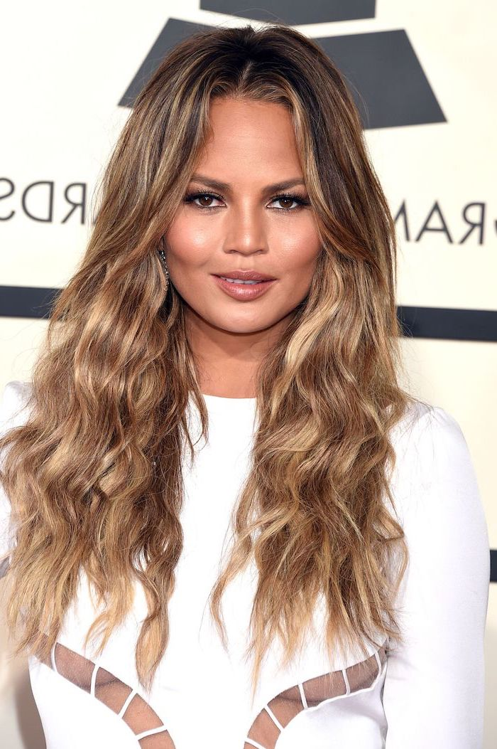 crissy teigen with long wavy hair, balayage caramel brown hair with highlights, fall hair colors for blondes, wearing white dress