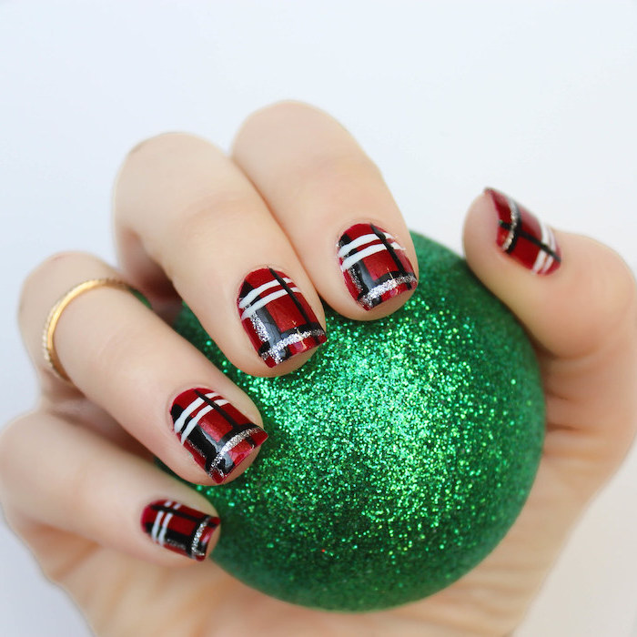 hand holding a green bauble, nail colors, plaid decorations on each nail, done with red black white and gold nail polish