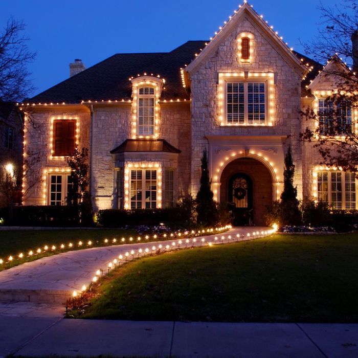 large two storey house, decorated with lots of lights, outdoor christmas decorations ideas, lights along the pathway