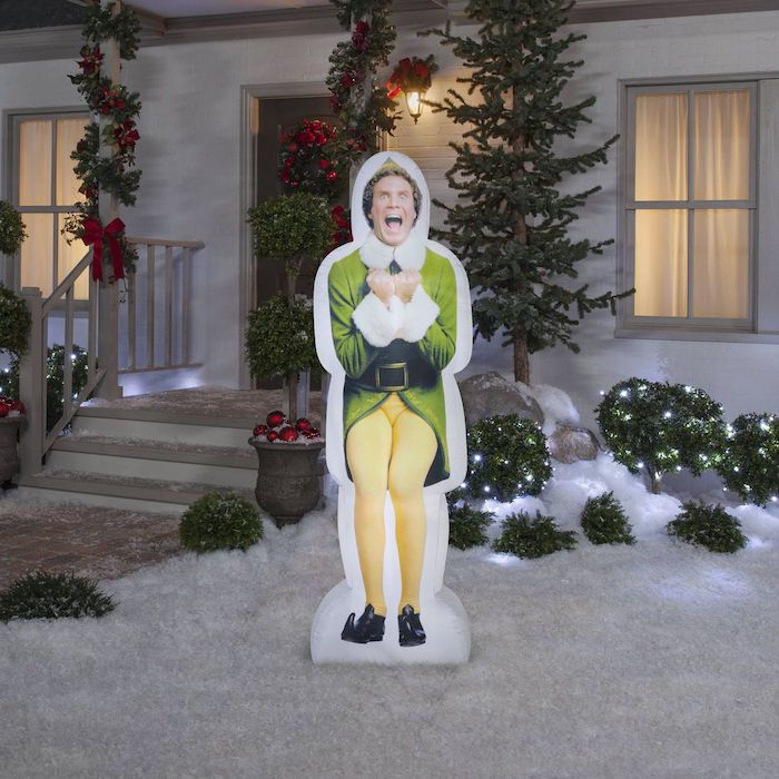 will ferrell character from movie elf, outdoor christmas tree lights, figurine placed in the snow, in the front yard