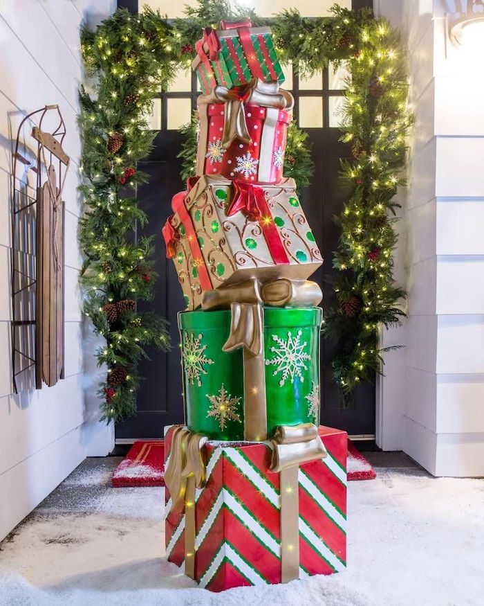 faux presents with lights, placed in the snow in front of a door, christmas porch decorations, wreath with lights on the door frame