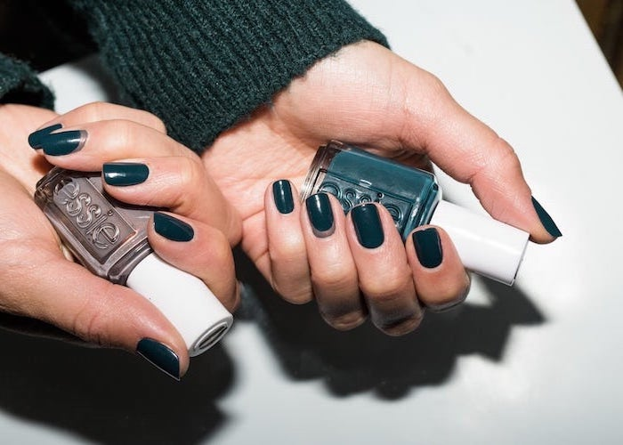 dark green nail polish on short squoval nails, neutral nail colors, two hands holding two different nail polish bottles