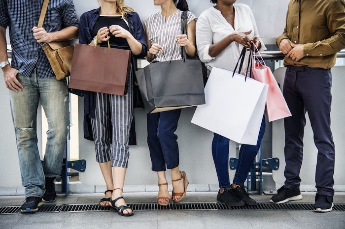 five people standing next to each other, holding shopping bags, benefits of shopping, three women and two men