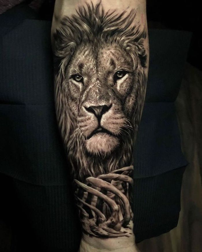 lion head with mane, bones in front of it, lion forearm tattoo, black background
