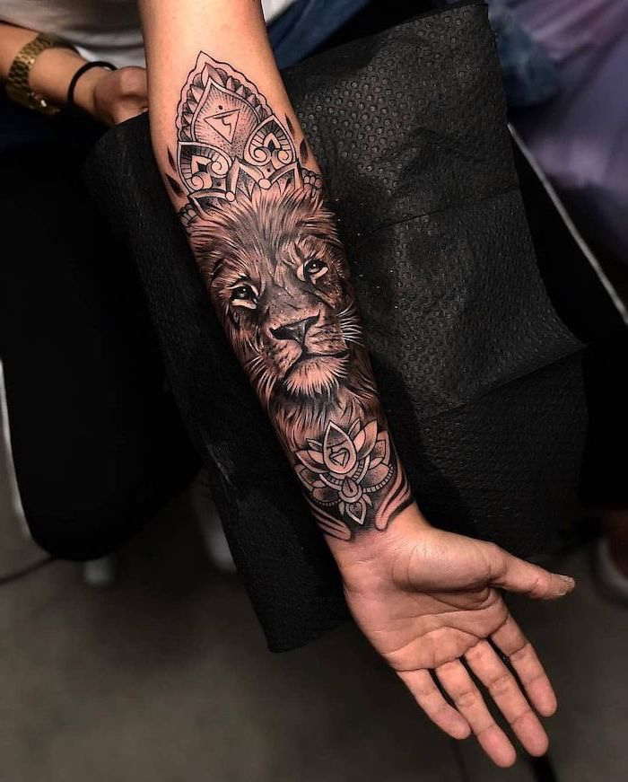 lion head surrounded by mandala lotus flowers, lion chest tattoo, forearm tattoo, black background