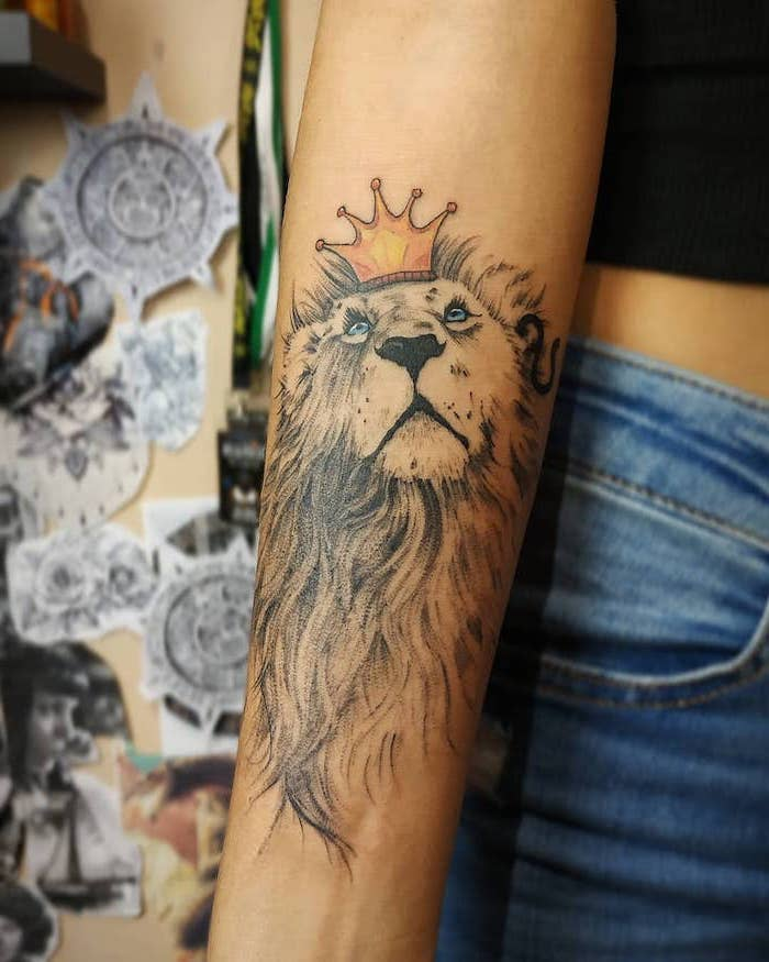 lion with long mane looking up, wearing a crown on its head, lion forearm tattoo, on woman wearing jeans and black top
