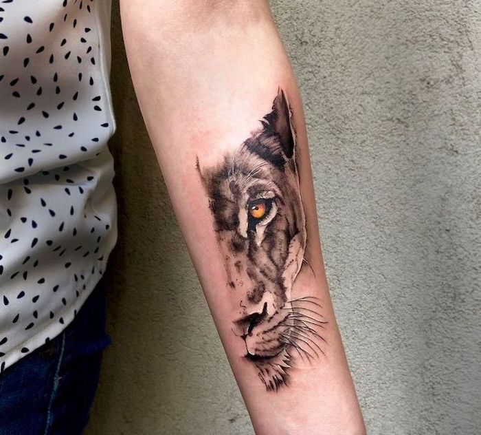 half of a lioness head with yellow eyes, forearm tattoo on woman, wearing jeans and white top, lion chest tattoo