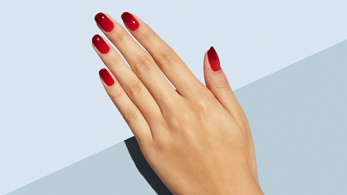 light to dark red gradient nail polish, ombre nails, short squoval nails on female hand, grey background