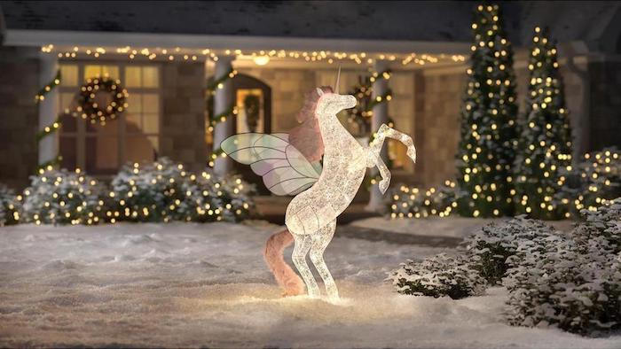 unicorn figurine, intertwined with lights, placed in the snow, in front of a house decorated with lights, christmas porch decorations